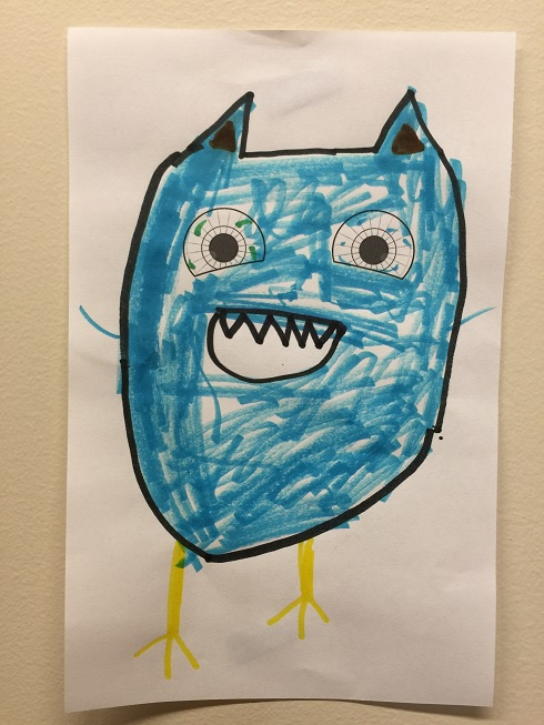 A child's drawing of a creature with a cat-like head, bird-like legs, and stick-figure arms